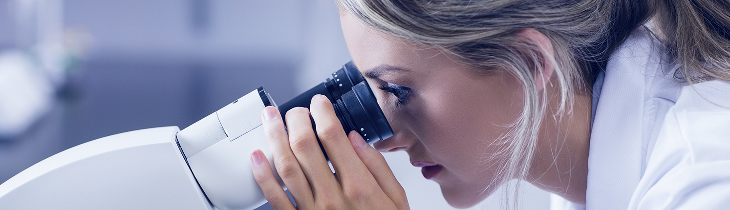 Pathologist looking through microscope in the lab